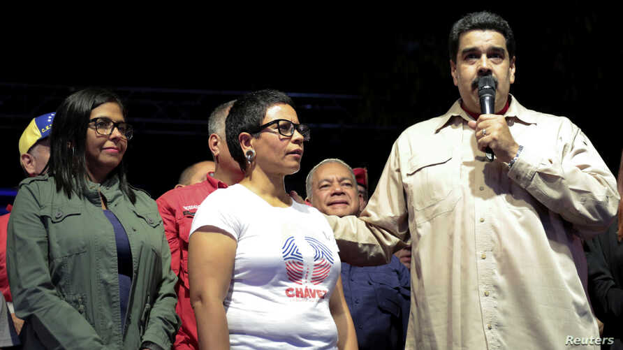Venezuela's President Nicolas Maduro (R) speaks during an event with supporters, next to newly elected mayor of Libertador district Erika Farias (C) and President of Venezuela's National Constituent Assembly Delcy Rodriguez (L), in Caracas, Venezuela