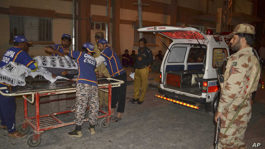 Pakistani volunteers unload the body of a man from an ambulance upon arrival at a hospital in Quetta, Pakistan, Sept. 10, 2017. Police said gunmen shot and killed four Shiite Muslims in an apparent sectarian attack.