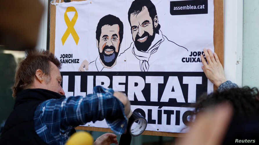 FILE - Activists put up banners with the photos of jailed leaders of Catalan pro-independence movements ANC (Catalan National Assembly) and Omnium Cutural, Jordi Sanchez and Jordi Cuixart, before Catalonia's former leader Carles Puigdemont addresses
