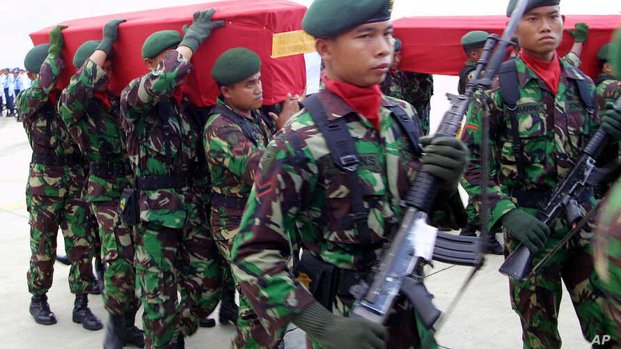 Indonesian soldiers carry the coffins of their colleagues who were killed in a clash with separatist rebels in Papua province upon arrival at Juanda airport in Surabaya, East Java, Indonesia, Tuesday, April 11, 2006.