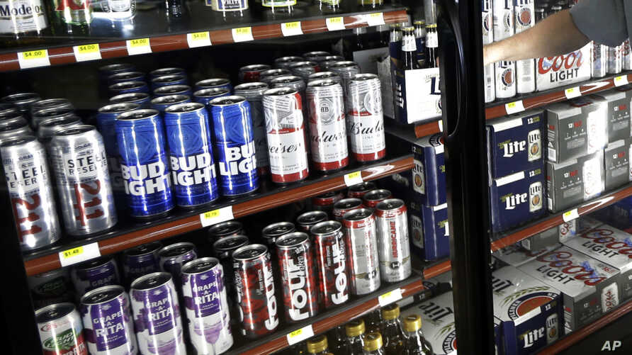 FILE - This April 19, 2017 file photo shows the beer cooler behind the counter in a convenience store in Sheridan, Indiana.