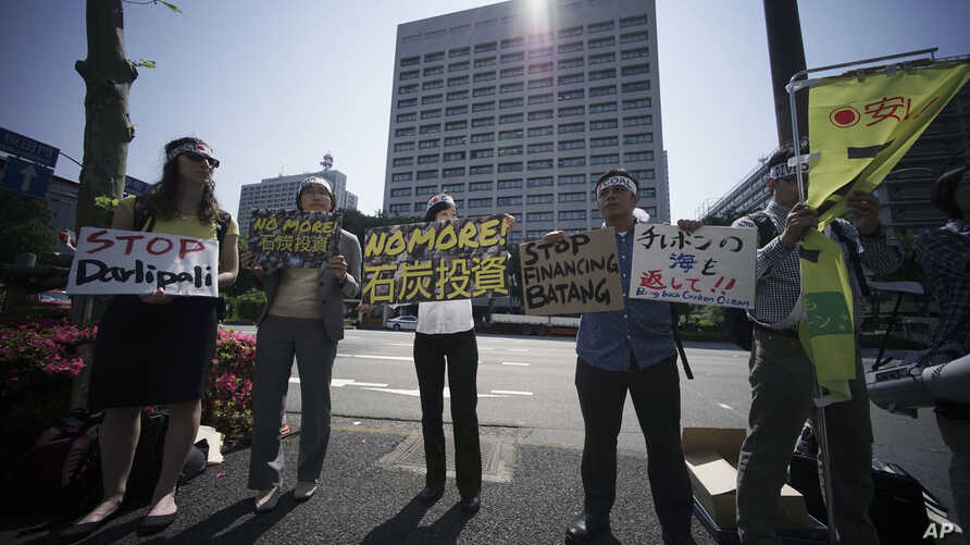 A group of people state a protest against climate change and coal investments, ahead of the G7 Finance Ministers and Central Bank Governors' Meeting, in front of the Ministry of Finance in Tokyo on May 19, 2016.