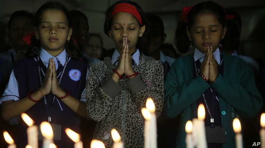 India schoolgirls offer prayers for victims killed in a Taliban attack on a Pakistan military-run school, in Mumbai, India, Dec. 17, 2014.