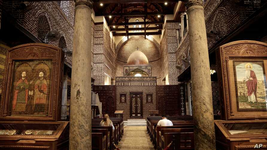 A man and woman pray at the Cavern Church, and the martyrs Sergius and Bacchus, famously known as the Abu Serga Church, in Old Cairo, Egypt, Aug. 30, 2016. Many of Egypt's Christians are infuriated by passage of a law giving authorities broad powers