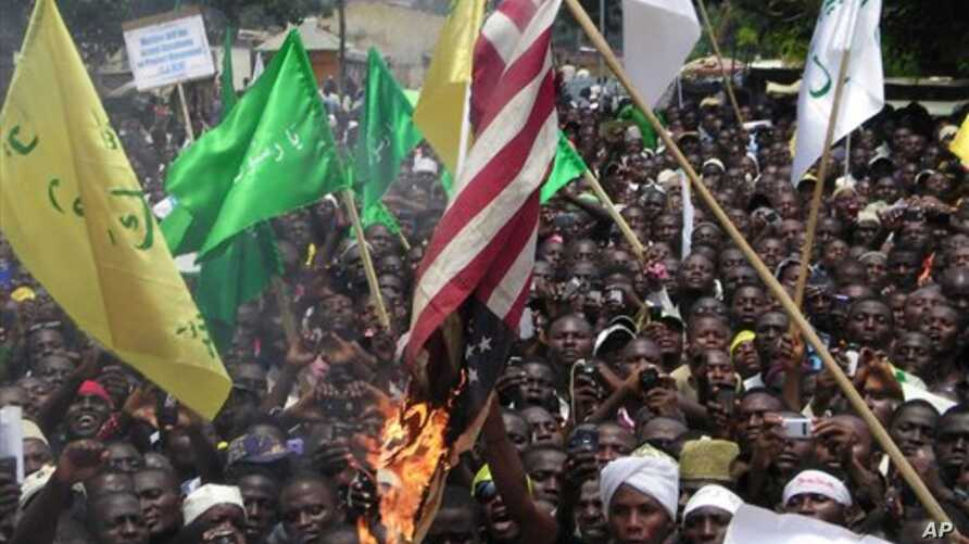 Muslims burn an American flag following a protest over an anti-Islam video that denigrates the Prophet Muhammad, in Kaduna, Nigeria, September 24, 2012. On the walls behind the protesters it reads: 'Death to the Americans, Death to the Israelites.