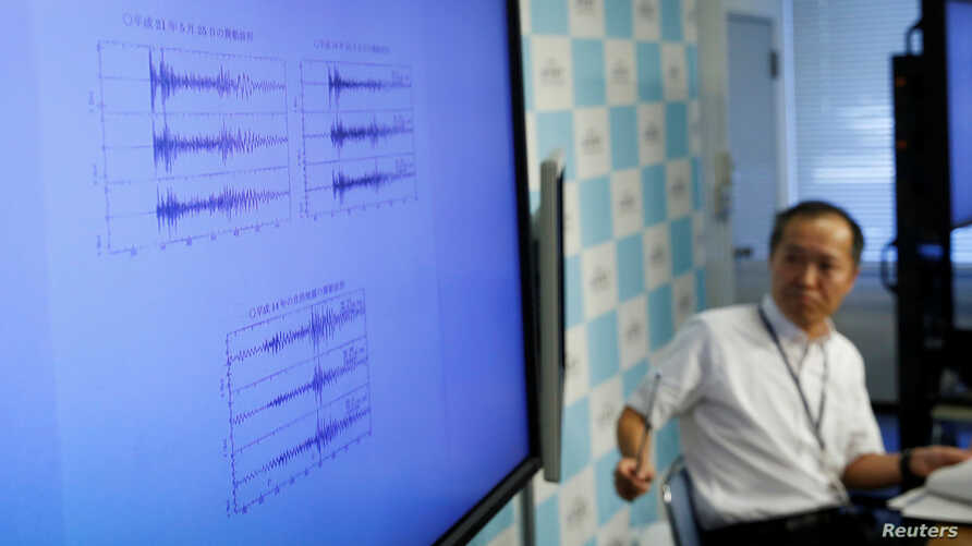 Japan Meteorological Agency's earthquake and tsunami observations division director Toshiyuki Matsumori speaks next to a monitor showing graphs of ground motion during a news conference at the agency, in Tokyo, Japan, Sept. 3, 2017.