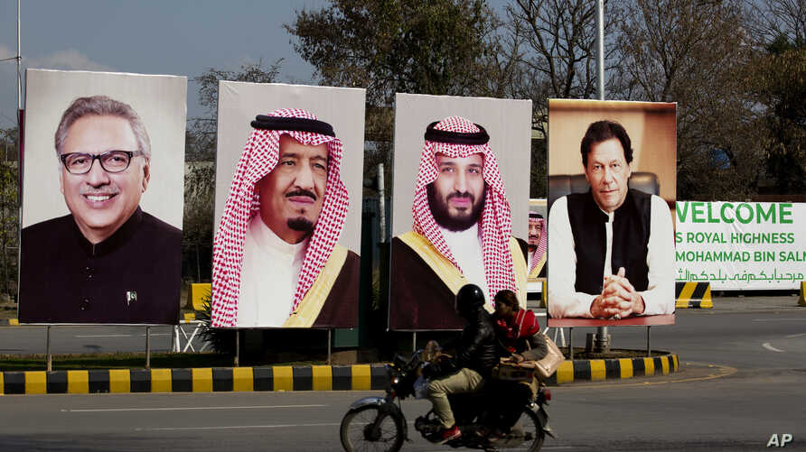 Pakistani riders drive past portraits of Pakistani and Saudi leaders displayed in Islamabad, Pakistan, Feb. 15, 2019.