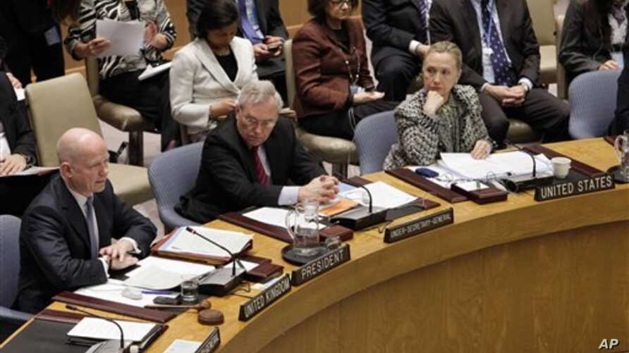 US Secretary of State Hillary Rodham Clinton, right, listens as  British Foreign Minister William Hague, left, addresses a Security Council meeting at United Nations headquarters, Monday, March 12, 2012.