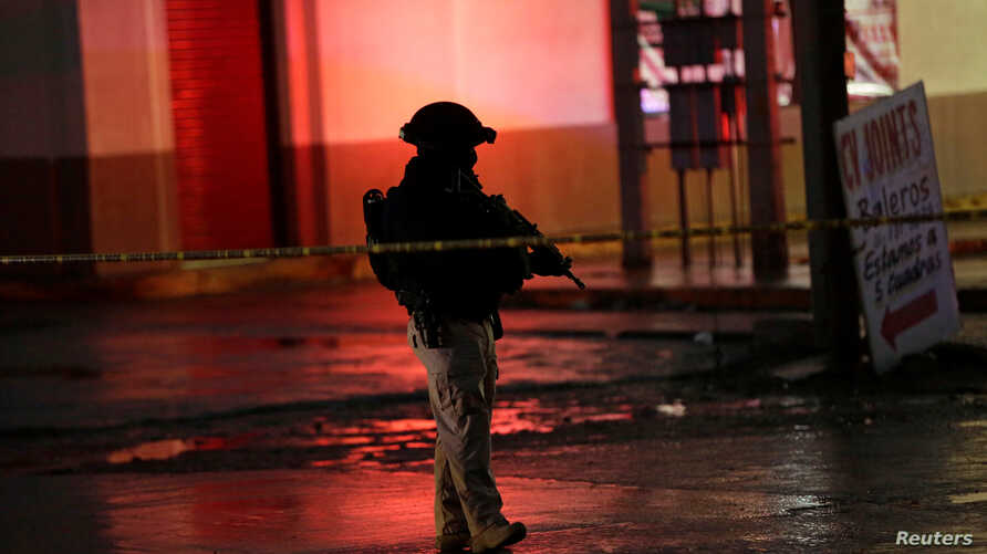 A state policeman keeps watch near a tire shop, which according to local media is the crime scene of a quadruple homicide, in Ciudad Juarez, Mexico, Dec. 6, 2017.