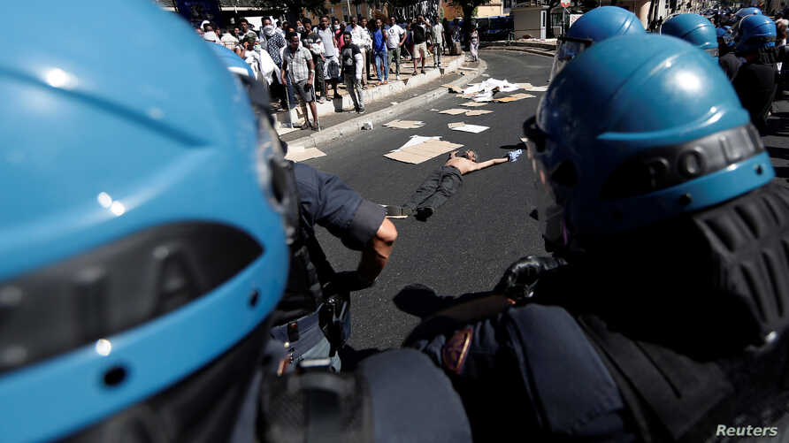 A refugee protests in the street after being forcibly removed from a building where he had been living, in central Rome, Aug. 23, 2017.
