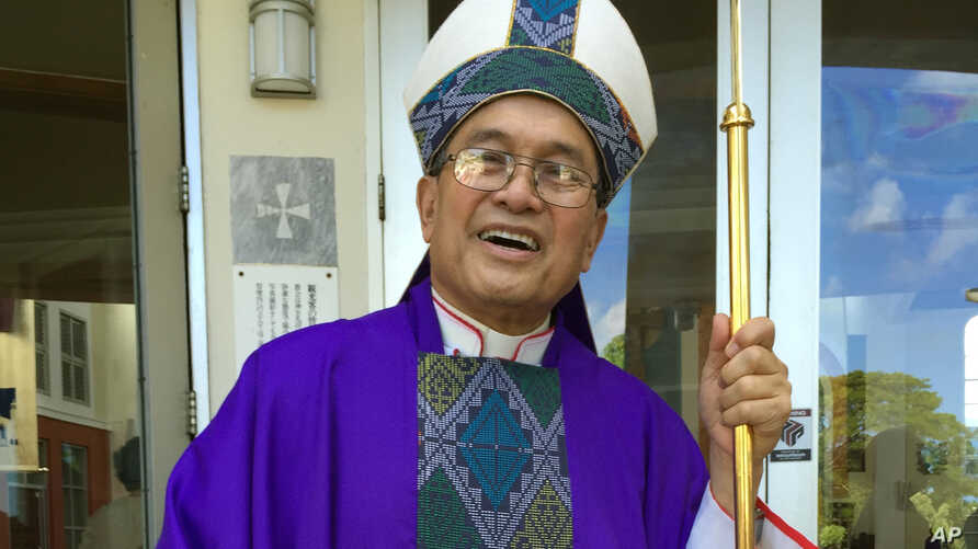 FILE - A Nov. 2014 photo shows Archbishop Anthony Apuron standing in front of the Dulce Nombre de Maria Cathedral Basilica in Hagatna, Guam. Apuron faces multiple allegations of sex abuse of altar boys in the 1970s. He has denied the claims.