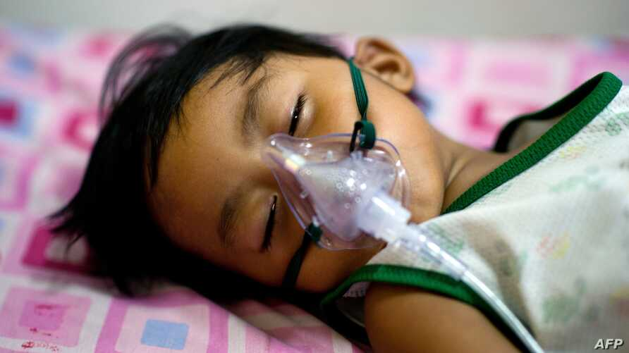 A boy with dengue fever receives medical oxygen while laying on a bed at the Quirino hospital in Quezon city in the suburbs of Manila, August 14, 2012.