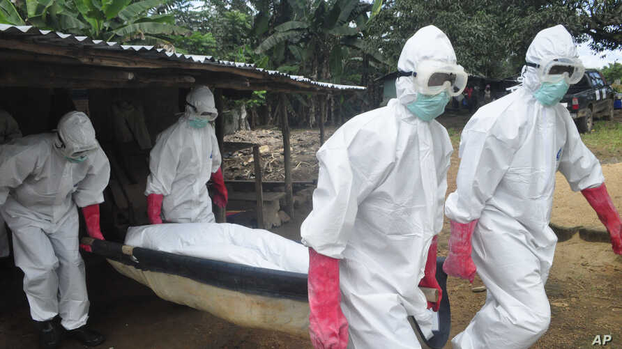 A burial team in protective gear carry the body of a woman suspected to have died from Ebola virus in Monrovia, Liberia. Oct, 18, 2014.