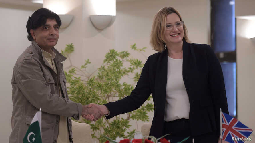 Pakistani Interior Minister Chaudhry Nisar Ali Khan (L) shakes hands with British Home Secretary Amber Rudd after an agreement signing on security issues in Islamabad, March 21, 2017.