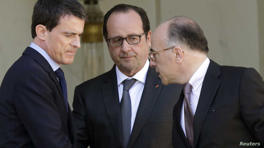 French President Francois Hollande (C) speaks with Interior minister Bernard Cazeneuve (R) and Prime Minister Manuel Valls at the end of the weekly cabinet meeting at the Elysee Palace in Paris, April 22, 2015.