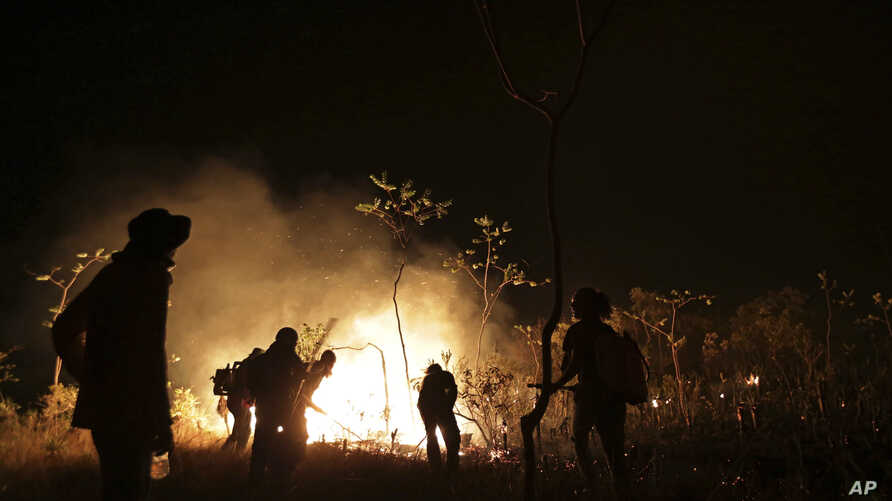 Locals work to contain a wild fire in the Chapada dos Veadeiros National Park in Goias state, Brazil, Oct. 28, 2017. Hundreds of men and women have joined forces with firefighters to help control the wildfire that has ravaged more than a quarter of t