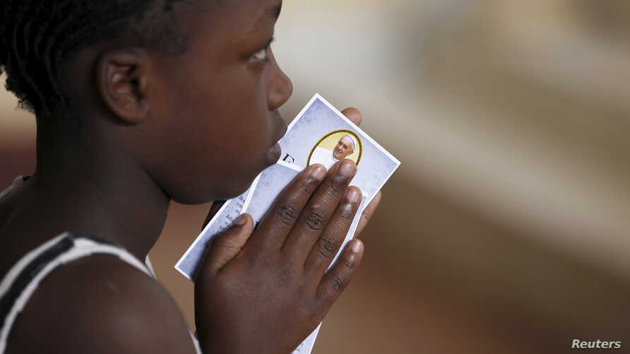 A child holds a prayer paper with the photo of Pope Francis during a special mass at St. Joseph the Worker Catholic Parish within Kangemi, a slum that is home to 650,000 people in Kenya's capital Nairobi, Nov. 22, 2015.