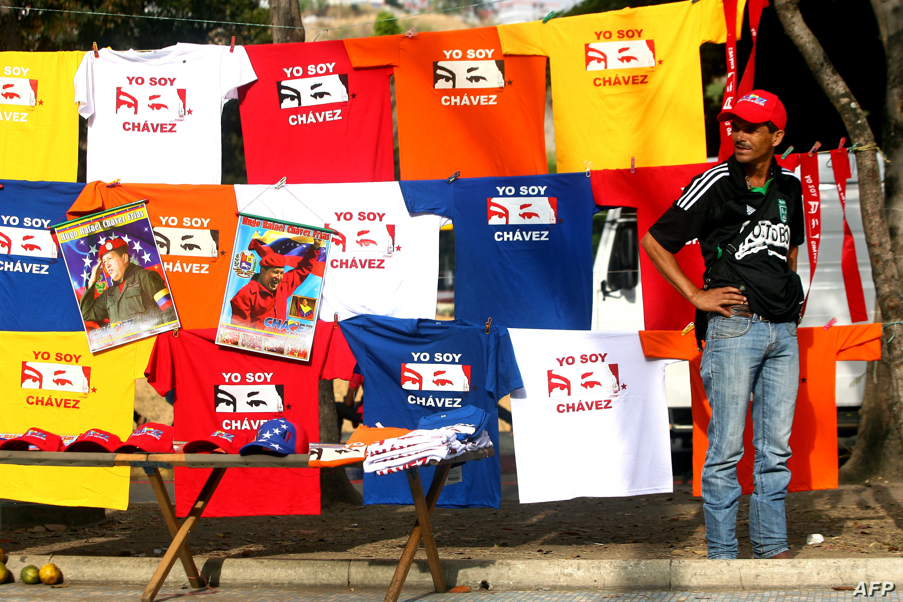 A peddler offer t-shirts with images of late Venezuelan President Hugo Chavez in front of the Military Academy in Caracas, Mar. 14, 2013.