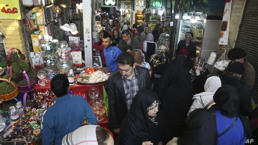 "FILE - People shop ahead of the Iranian New Year, or Nowruz, meaning ""New Day"" at the Tajrish traditional bazaar in northern Tehran, Iran, March 13, 2019."