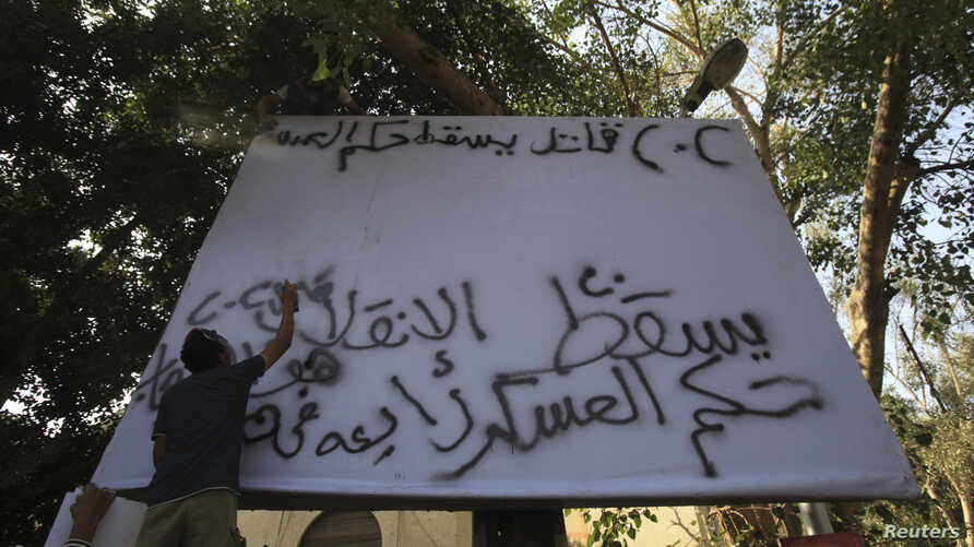 """Supporters of the Muslim Brotherhood and ousted Egyptian President Mohamed Mursi spray """"Down with military rule - Sisi killer"""" on a billboard during a protest against the military and interior ministry in the fashionable Maadi suburb in Cairo, Novemb"""