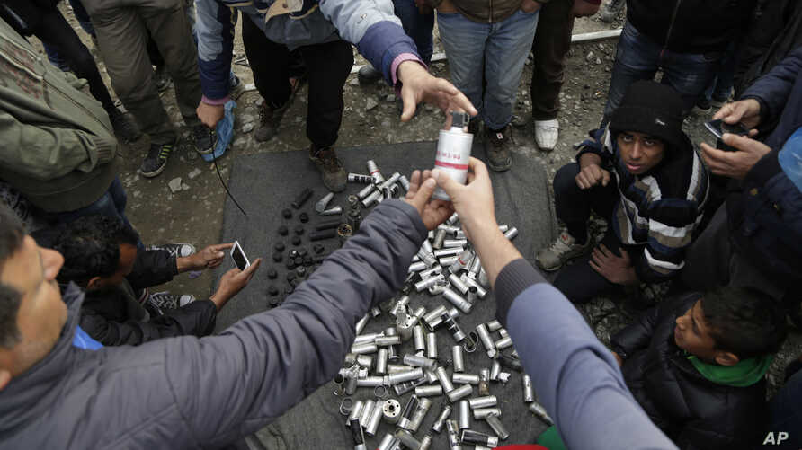 Migrant men display used tear gas canisters apparently used by Macedonian police during yesterday riots at the fence in the makeshift camp of the northern Greek border point of Idomeni, Greece, Monday, April 11, 2016.