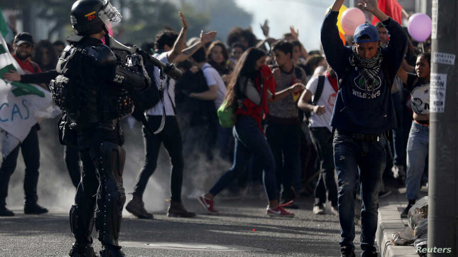 Riot police confront students of public universities during a march in Bogota, Colombia, Dec. 13, 2018.