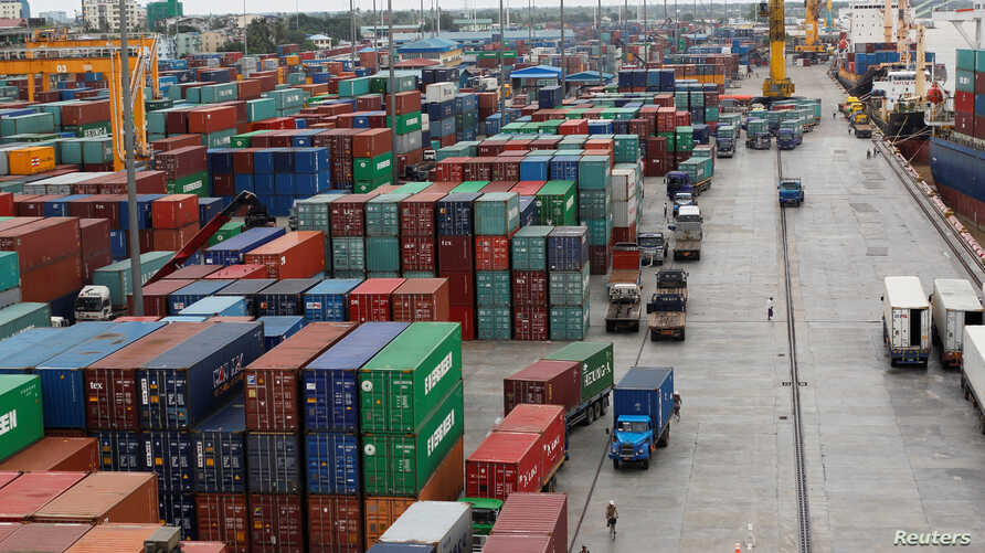 Workers are seen among the containers at Asia World port in Yangon, Myanmar, July 2, 2014.