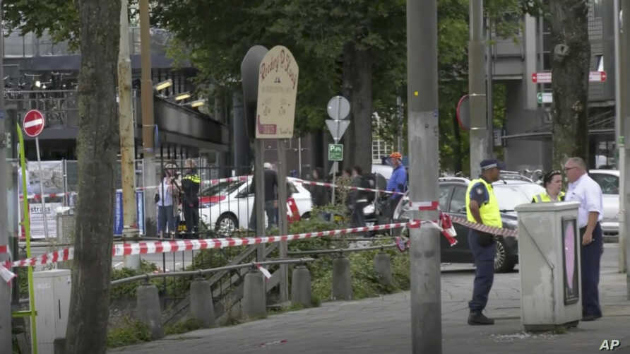 In this image made from video, Dutch police officers stand near the scene of a stabbing attack near the central daily station in Amsterdam, the Netherlands, Aug. 31, 2018.