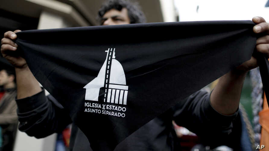 "A seller offers handkerchiefs reading in Spanish ""Church and state — Separate issues"" in Buenos Aires, Argentina, Aug. 18, 2018. People formed lines Saturday as part of a nationwide movement in the homeland of Pope Francis to renounce their religious"
