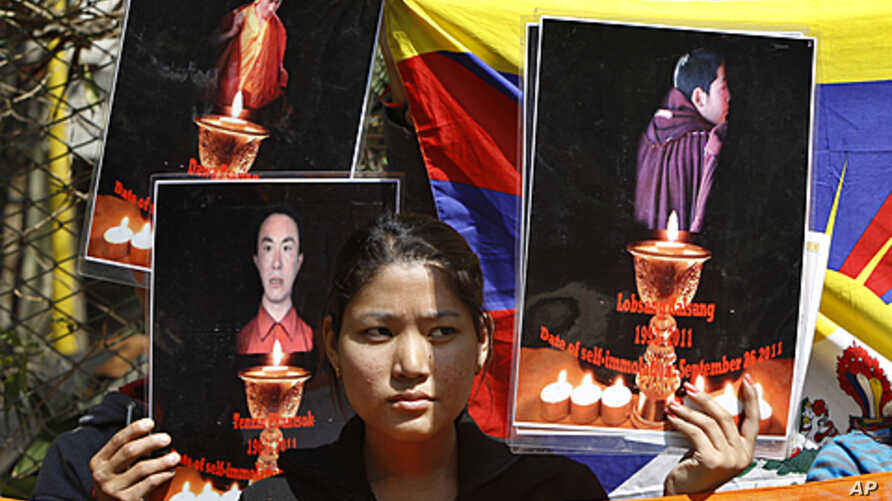 A Tibetan exile holds the photographs of Tibetan monks who have self immolated in Tibet protesting Chinese government, during a demonstration to support three fellow Tibetan exile students Tselo Gyal, 21, Lugoen Thar, 21, and Gyaltsen, 19 in Bangalor