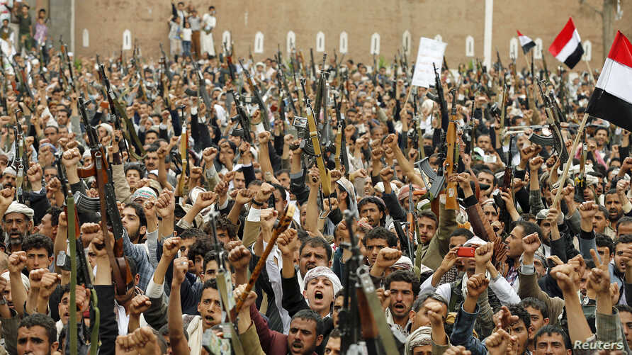 Shi'ite Muslim rebels hold up their weapons during a rally against air strikes in Sanaa, Yemen, March 2015.