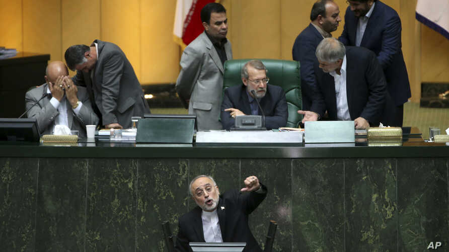 Head of Iran's Atomic Energy Organization Ali Akbar Salehi, bottom, speaks in an open session of parliament while discussing a bill on Iran's nuclear deal with world powers, in Tehran, Iran, Oct. 11, 2015.