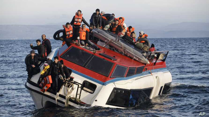 Refugees and migrants sit atop a heavily-listing small vessel as they try to travel from the Turkish coast to Skala Sykaminias on the northeastern Greek island of Lesbos, Oct. 30, 2015.