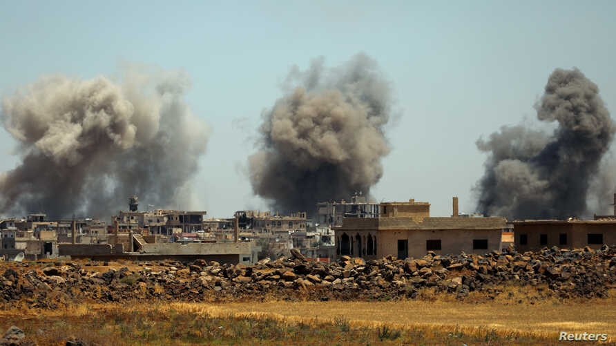 Smoke rises from al-Harak town, as seen from Deraa countryside, Syria, June 25, 2018.