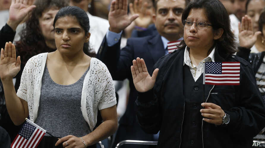 FILE - Immigrants take the citizenship oath during naturalization ceremonies at a U.S. Citizenship and Immigration Services (USCIS) ceremony in Los Angeles, California, Sept. 20, 2017.