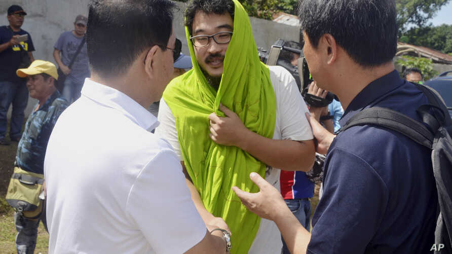South Korean hostage Park Chul-hong (center) is greeted by unidentified officials as he prepares to board a plane for Davao city following his release Jan. 14, 2017, from his kidnappers in the volatile island of Jolo, southern Philippines. Park and F