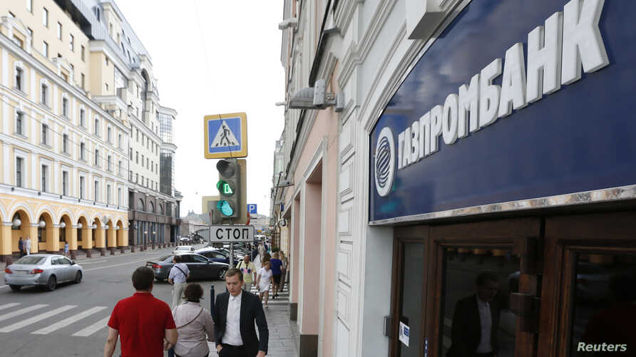 People walk past an office of Gazprombank, Russia's central bank, in Moscow, July 17, 2014.