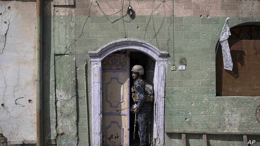 A federal policeman exits a house after searching it during fighting against Islamic State militants, on the western side of Mosul, Iraq,  March 29, 2017.