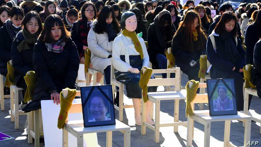 """People sit around a statue of a """"comfort woman"""" during an installation of empty chairs during a performance event, commemorating the death of eight former sex slaves this year, in Seoul, South Korea."""