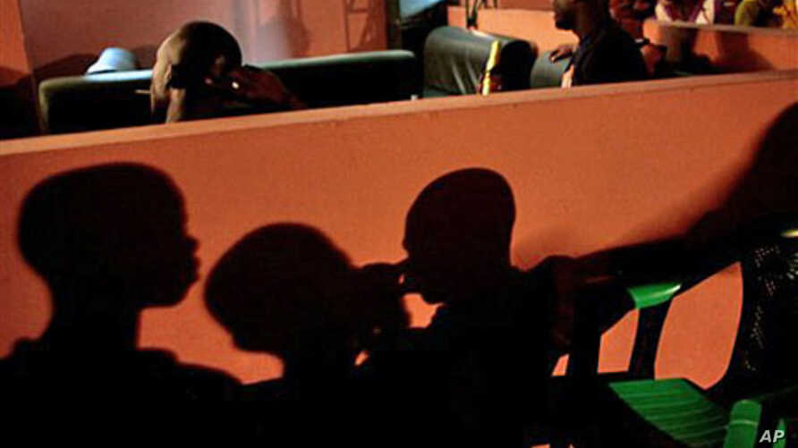 Residents watch TV in Abidjan, 03 Nov 2010, as election results set the stage for a runoff election