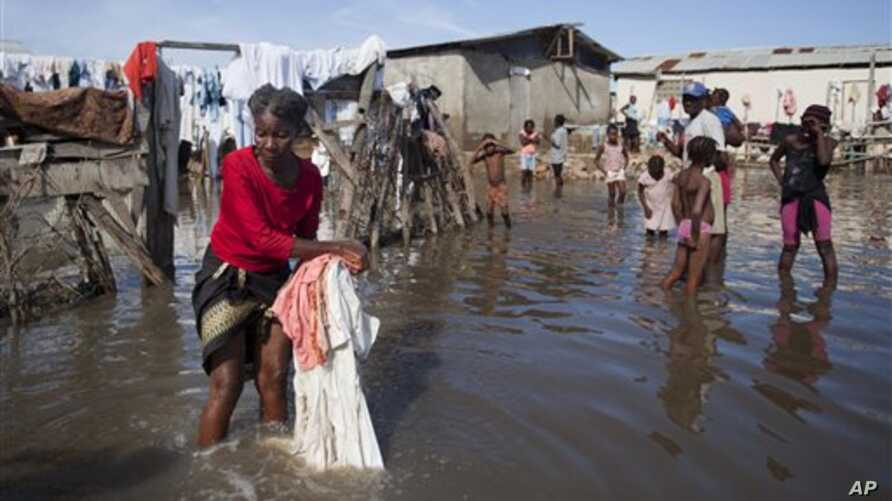 Bernard Sylphanie cleans her belongings in floodwater outside her home in Cap-Haitien, Haiti, Friday, Nov. 7, 2014. Thousands of families in Haiti and the neighboring Dominican Republic have been affected by floods from a storm system that drenched t