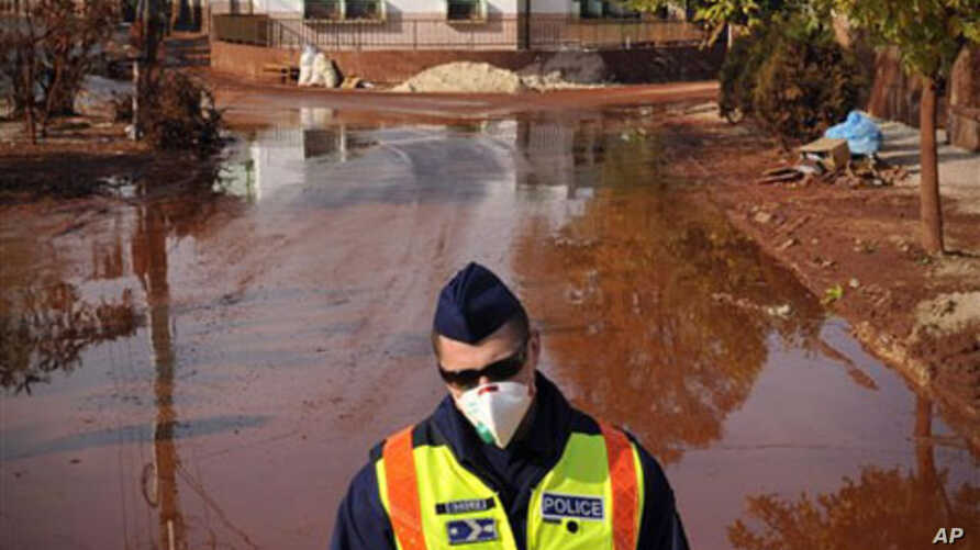 A Hungarian police officer wearing a protective mask guards a street covered by toxic red sludge in Devecser, Hungary, 13 Oct 2010