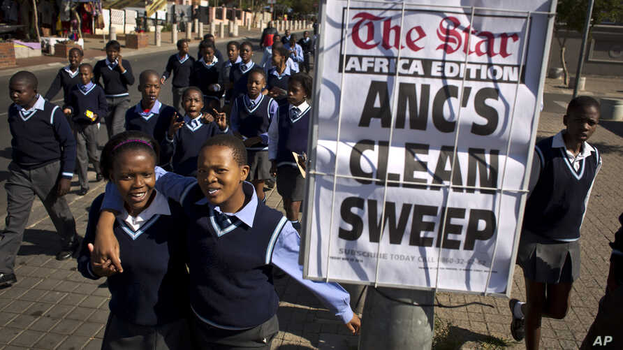 Schoolchildren walk past a newspaper placard reporting the election victory of Jacob Zuma's African National Congress (ANC) party, based on preliminary results, in the Soweto township of Johannesburg, South Africa, May 9, 2014.