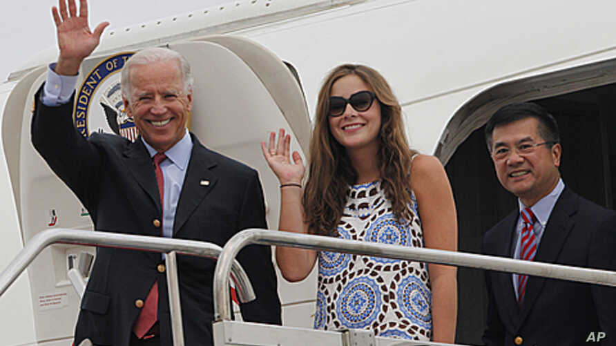 US Vice President Joe Biden, left, waves with his granddaughter Naomi Biden, center, and US Ambassador to China, Gary Locke, right, as they walk out from the Air Force Two upon arrival at the airport in Chengdu, China, August 20, 2011