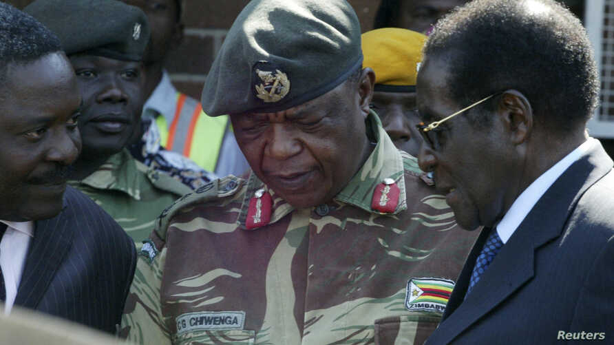 FILE - Zimbabwe's President Robert Mugabe, right, talks to General Constantine Chiwenga upon his arrival at Harare International Airport, July 4, 2008.