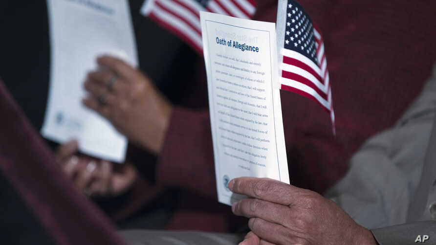 """FILE - Participants hold the """"Oath of Allegiance"""" and American flags during a naturalization ceremony at the National Archives in Washington, Dec. 15, 2015."""