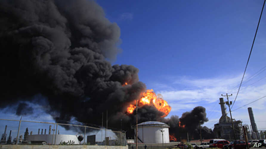 Plumes of black smoke and flames continue to rise over the Amuay refinery near Punto Fijo, Venezuela,  Aug. 27, 2012.
