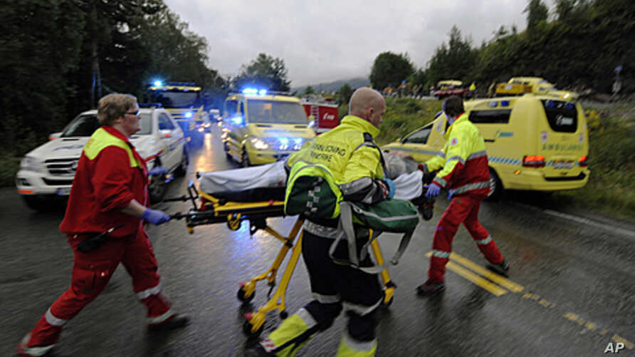 Rescue personnel push an injured victim away from the camp site in Utoeya, Norway, July 23, 2011