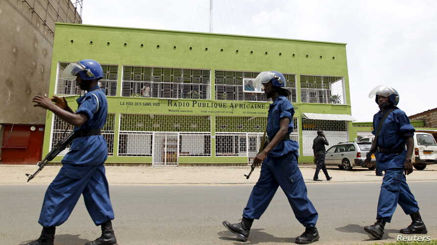 FILE - Riot policemen are seen walking outside the Radio Publique Africaine broadcasting studio in Burundi's capital, Bujumbura, Apr. 26, 2015.
