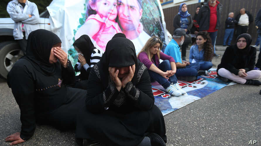 Families of Lebanese soldiers who were kidnapped by Islamic militants, block a main road during a protest after an al-Qaida-linked group in Syria says it has killed a kidnapped soldier Ali Bazzal, seen in poster with his daughter, in downtown Beirut,